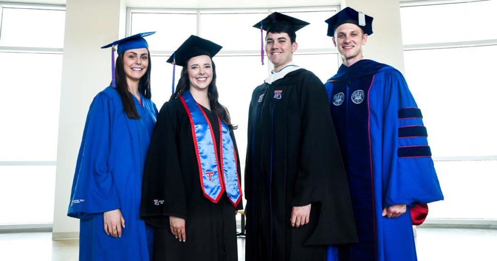Four students modeling Louisiana Tech's new commencement regalia.
