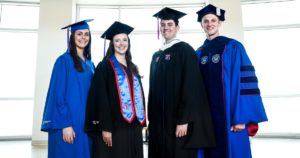 Four students modeling Louisiana Tech's new commencement regalia.
