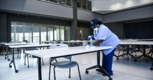 Essential worker, April Austin cleaning student work stations in IESB.