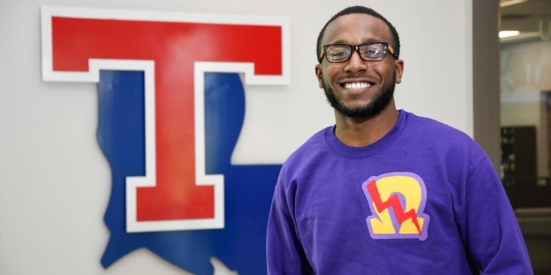 Nicholas Cobb standing in front of the Louisiana Tech University state and T logo.