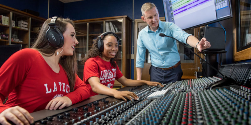 Michael Austin, Founding Director of the School of Music, works with students on a soundboard.