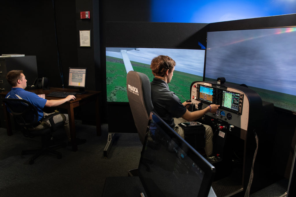 An aviation student trains for flight using a simulator in Davison Hall